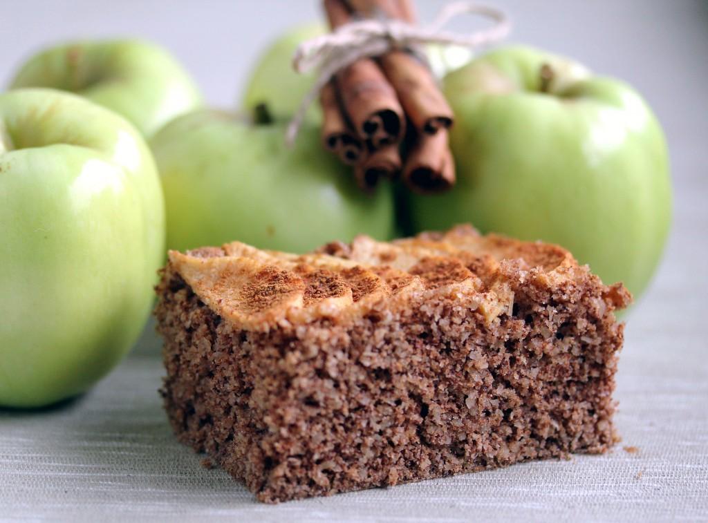 Karppaajan syksyinen omena-kanelikakku, pala, taustalla omenoita ja kanelitankonippu